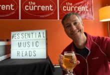 Jay holding cider in front of ESSENTIAL MUSIC READS sign
